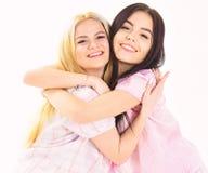 Meninas que abraçam firmemente, isolado no fundo branco Irmãs ou melhores amigos nos pijamas Louro e morena no sorriso imagens de stock royalty free