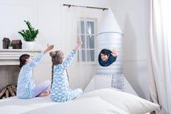 Meninas que acenam as mãos ao menino no foguete ao jogar cosmonautas Imagens de Stock Royalty Free
