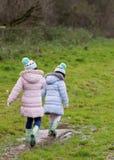 Meninas que andam através de uma poça enlameada Fotografia de Stock