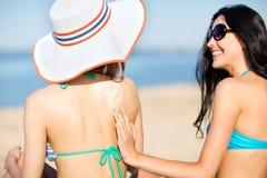 Meninas que aplicam o creme do sol na praia Imagens de Stock Royalty Free
