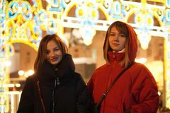 Meninas que apreciam a época de férias do inverno Luzes de Natal borradas no fundo, crepúsculo fotos de stock