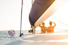Meninas que apreciam o por do sol no mar e no iate Fundo abstrato da navigação Fotografia de Stock
