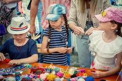 Meninas que aprendem fazer guardanapo de tabela coloridos na oficina de confecção de malhas fotos de stock
