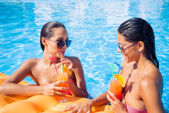 Meninas que bebem cocktail na piscina Fotos de Stock