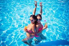 Meninas que bebem cocktail na piscina Foto de Stock Royalty Free
