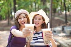 Meninas que bebem o chá da bolha e para apreciar férias de verão imagens de stock
