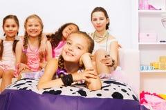 Meninas que colocam e que sentam-se junto na cama grande Imagem de Stock