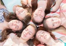 Meninas que colocam na terra que olha acima, alguns com os olhos fechados Fotografia de Stock Royalty Free