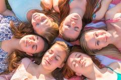 Meninas que colocam na terra que olha acima, alguns com os olhos fechados Foto de Stock