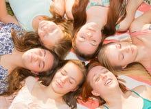 Meninas que colocam na terra que olha acima, alguns com os olhos fechados Fotos de Stock Royalty Free