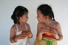 Meninas que comem hamburgueres imagem de stock royalty free