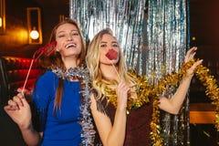 Meninas que comemoram a v?spera de anos novos no clube noturno fotografia de stock