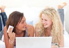Meninas que compram em linha em um quarto Fotografia de Stock Royalty Free
