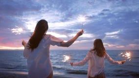Meninas que correm ao longo da praia com chuveirinhos filme
