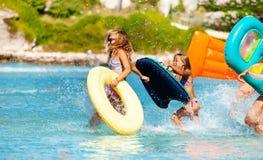 Meninas que correm no mar com material inflável fotografia de stock royalty free