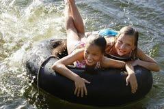 Meninas que encontram-se no tubo do flutuador no lago imagem de stock
