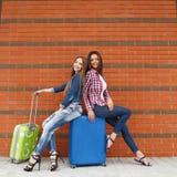 Meninas que esperam o trem que senta-se na mala de viagem Fotografia de Stock Royalty Free