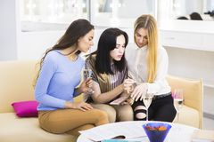 Meninas que falam, cosméticos de tentativa e champanhe bebendo Fotografia de Stock