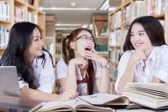 Meninas que falam e que riem na biblioteca Fotografia de Stock Royalty Free