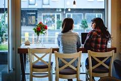 Meninas que falam na frente do portátil no café Fotos de Stock