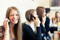 Meninas que falam no telefone celular no bar Fotos de Stock