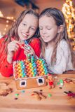 Meninas que fazem a casa de pão-de-espécie do Natal na chaminé na sala de visitas decorada fotos de stock royalty free