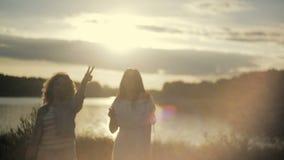 Meninas que fazem a paz para o por do sol pela beira do lago Fêmeas novas salto, acenando seu cabelo em uma luz do sol brilhante vídeos de arquivo