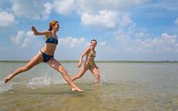 Meninas que funcionam e que saltam acima da água Foto de Stock