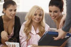 Meninas que olham o álbum de fotografias em casa Imagem de Stock