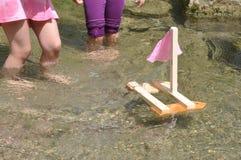 Meninas que jogam com o barco na água foto de stock royalty free