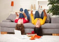 Meninas que lêem upside-down no sofá Imagens de Stock