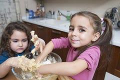 Meninas que misturam a massa com as mãos Imagens de Stock