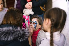 Meninas que pintam as caras às crianças uma classe mestra na abertura de um centro do ` s das crianças em Cherkasy, Ucrânia, o 23 imagem de stock