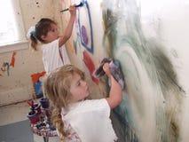 Meninas que pintam a parede Imagem de Stock