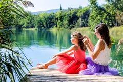 Meninas que relaxam ao lado do lago fotografia de stock