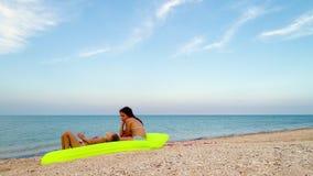 Meninas que relaxam em um colchão de ar no beira-mar video estoque