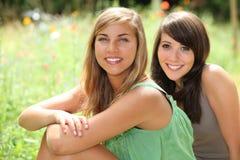 Meninas que sentam-se em um campo imagens de stock