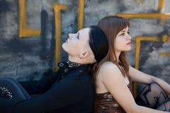 Meninas que sentam-se na frente da parede dos grafittis Imagens de Stock Royalty Free