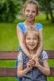 Meninas que sentam-se no banco Foto de Stock Royalty Free