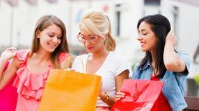 Meninas que sentam-se no banco com sacos de compras Imagens de Stock