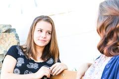 Meninas que sentam-se no banco junto Fotografia de Stock Royalty Free