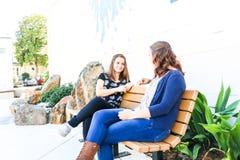 Meninas que sentam-se no banco junto Fotos de Stock Royalty Free
