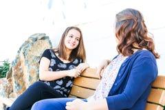 Meninas que sentam-se no banco junto Imagens de Stock Royalty Free