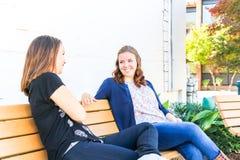 Meninas que sentam-se no banco junto Imagem de Stock