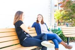 Meninas que sentam-se no banco junto Foto de Stock