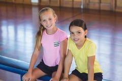 Meninas que sentam-se no banco no campo de básquete Fotos de Stock