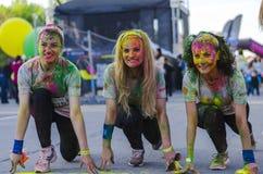 Meninas que sorriem com pó colorido imagem de stock