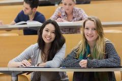Meninas que sorriem no salão de leitura com PC da tabuleta Imagens de Stock Royalty Free