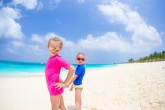 Meninas que têm o divertimento na praia tropical durante férias de verão Fotos de Stock