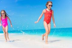 Meninas que têm o divertimento na praia tropical que joga junto na água pouco profunda Fotos de Stock